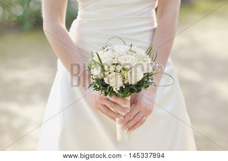 Wedding bouquet of white roses in bride's hand