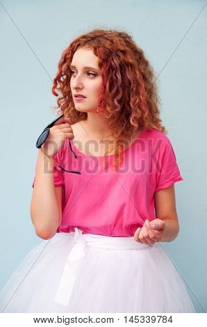 Curly hair woman with colorful hair dye wearing bright pink tee shirt and full skirt and holding black sunglasses
