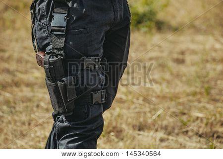 The gun hidden in a holster hanging on a soldier's leg.