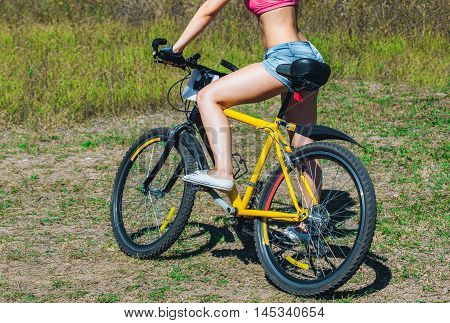 Girl athlete in jeans short shorts riding a bike in the park.