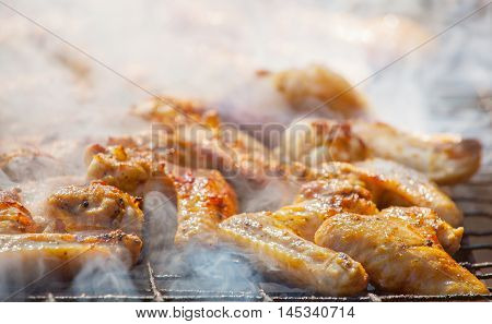 Marinated fried with a crispy golden crust fried chicken wings on the grill.