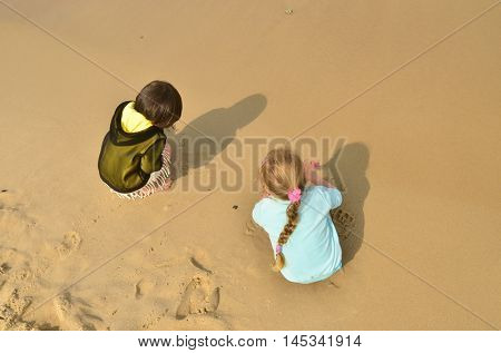 Children playing on sandy beach. Girls are four years old. View from top. Sand is wet.