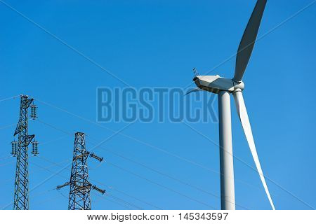 Detail of a white wind turbine with a power line (two high voltage towers) on a clear blue sky