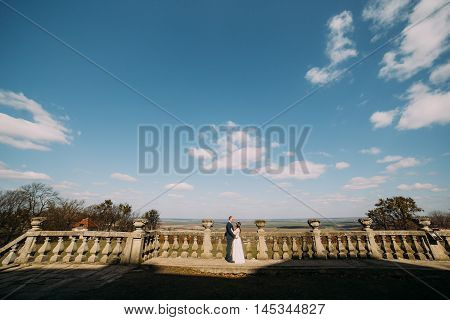 Wedding portrait of happy stylish newlywed bride and groom posing at old stone terrace in spring park with magnificent cloudy sky landscape.