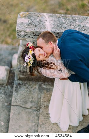Happy groom sagging his pretty bride while kiss her on antique stone stairs. High angle view.