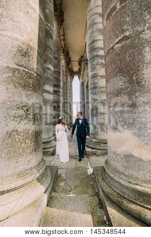 Young wedding couple posing between rows of antique building columns.