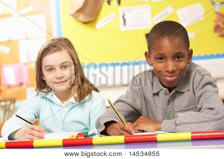 Schoolgirl And Schoolboy Studying In Classroom