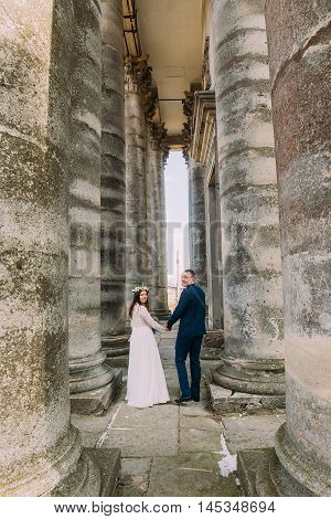 Young attractive wedding couple posing between rows of antique building stone columns.