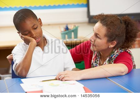 Unhappy Schoolboy Studying In Classroom With Teacher