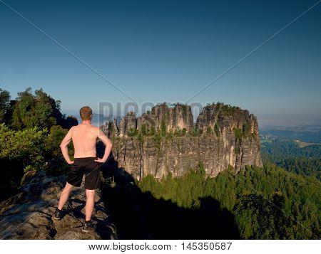 Naked Man In Black Pants On Rock Side.  Sharp Sandstone Cliffs