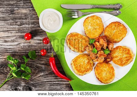 potatoes pancakes with stewed pork meat on white dish fork and knife on green table mat sour cream in gravy boat on old wooden background view from abiove