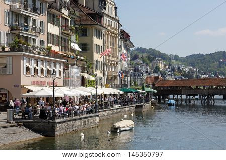 LUCERNE SWITZERLAND - MAY 08 2016: Cafes and buildings along river Reuss shows its unique character and variety of sightseeing attractions. The town is a destination for many travelers