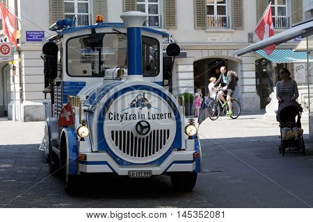 LUCERNE SWITZERLAND - MAY 08 2016: Blue and White Trackless Train travels through the streets of the city providing a convenient way for tourists to see variety of sightseeing attractions