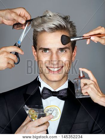 Beautiful man surrounded by the multifunctional service (stylist and hairdresser). Photo of charming man ready to step out in style James Bond. Grooming himself