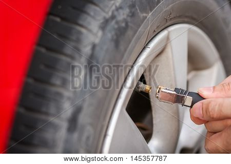 Filling air into a grungy car tire to increase pressure