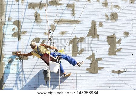 Sofia, Bulgaria - August 25, 2016: A worker putting on a building's thermal and noise isolation is working hanging on ropes on the wall of the building.