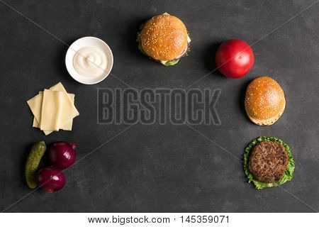 Beef burger with lettuce and sauce on the black chalkboard. Ingredients of popular takeaway food