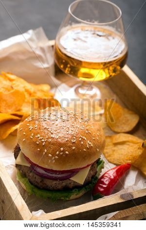 Beef burger with lettuce and beef cutlet. Potato chips and glass of beer