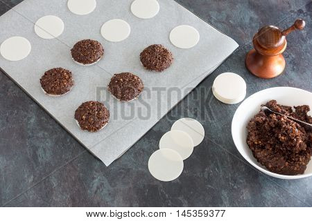 Baking German Gingerbread. A baking tray full of gingerbread, a bowl with gingerbread dough and round wafers.
