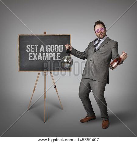 Set a good example text on  blackboard with drunk businessman