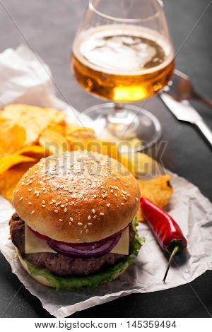 Beef burger with lettuce and minced meat cutlet. Potato chips and glass of beer