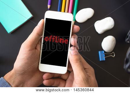 Offline, text message on screen at hands take smartphone, black table with office supplies backdrop background . business concept