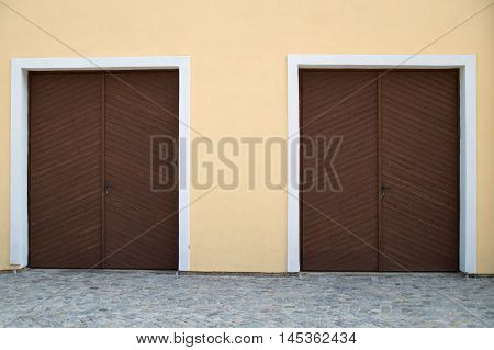 Two brown wooden garage doors on yellow house