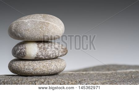 stacked rounded stone pebble arrangement in gradient grey back