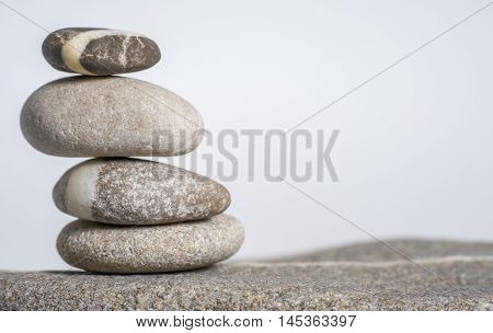 stacked rounded stone pebble arrangement in light grey back