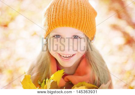 girl in an orange cap smiles and glad a autumn