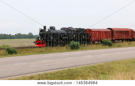 Swedish steam freight train between a road and a field on a cloudy overcast day