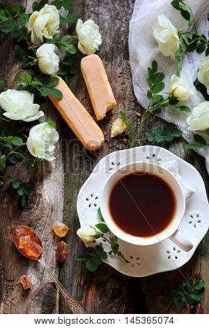 cup of black tea and rosehip flowers on wooden boards