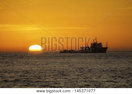 Fishing vessel trawling off the East Coast of the UK at sunrise. The trawler is shown in silhouette against a natural vivid orange sky as the sun rises from the surface of the water.