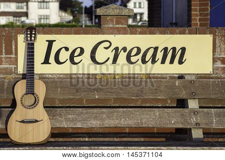 Parlour-sized classical acousic guitar resting on a bench infront of an ice cream sign. Symbolic of vacation relaxation and seaside fun.