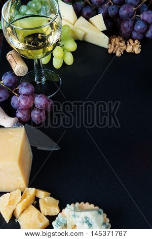 White wine various types of cheese walnuts and grapes on a black slate stone background