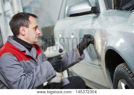 colourist man compare color sample with car paint