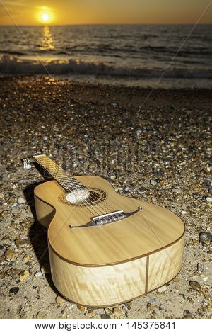 A classical parlour sized acoustic guitar laying on the shore at sunrise or sunset. The image is symbolic of vacation and the aftermath of a beach party