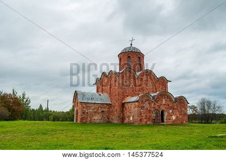 Architecture summer landscape in cloudy weather - Church of the Transfiguration of Savior on Kovalevo in Veliky Novgorod Russia. Architecture view of church under stormy dramatic sky.