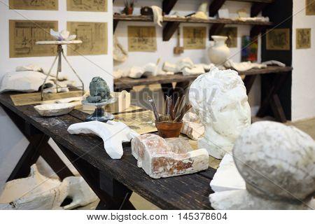 Desktop of sculptor with plaster head, tools, plaster pieces in empty workshop