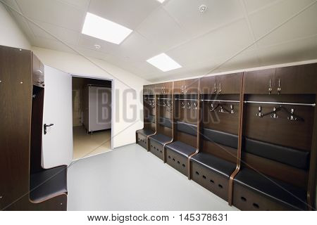 Empty room for sports judges in stadium - lockers and hangers for clothes