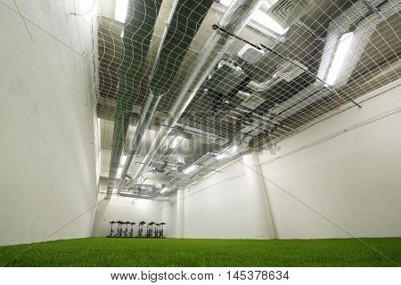 Room with artificial green grass in stadium for training of football players