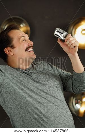 Smiling man with mustache poses with microphone in studio with lamps on wall