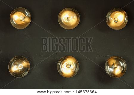 Six round lamps with lamp shades are on black wall in studio