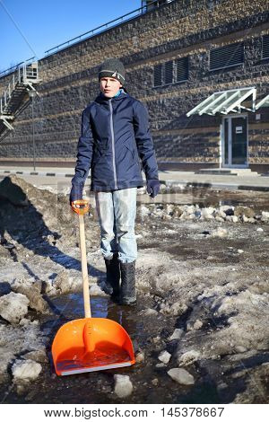 Boy in black stands with shovel among melted snow at sunny spring day