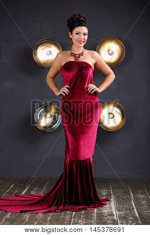 Smiling woman in red velvet dress poses near wall with lamps in studio