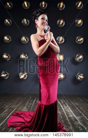 Pretty girl in red stands with microphone near wall with lamps in studio