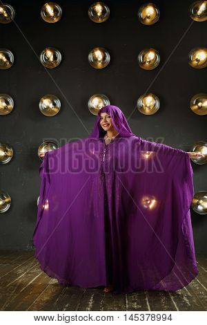 Woman in purple mantle poses near wall with lamps in studio and smiles