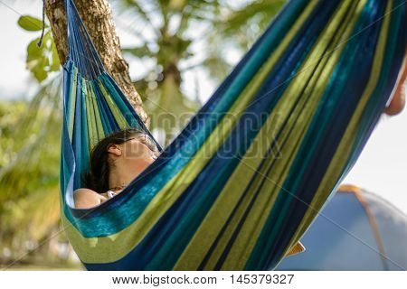 Woman taking a nap on a hammock in the beach