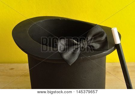 A magicians hat displayed with a wand and bow tie