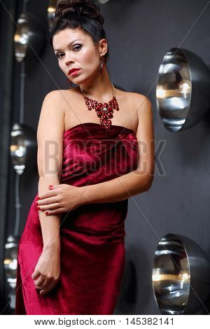 Pretty girl poses in velvet dress near wall with lamps in grey studio